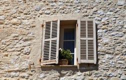 La finestra rustica con i vecchi otturatori di legno in casa rurale di pietra, risulta fotografia stock