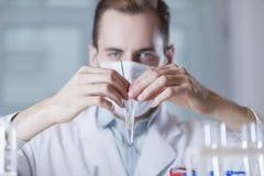 La fiole avec l'usine devant le visage du scientifique Photographie stock libre de droits