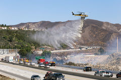 LA Fire Department helicopter dropping fire retardant near freeway Royalty Free Stock Image