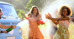 La fissuration d'homme de hippie ouvrent une bouteille de champagne sur ses amis clips vidéos