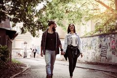 La fixation de couples remet à l'extérieur Jeunes couples waling sur la rue Image libre de droits
