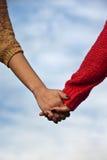 La fixation de couples remet le fond bleu image stock