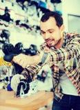La fixation masculine de réparateur fait du patin à roulettes dans le magasin de sports Photos libres de droits