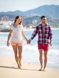 La fixation remet des couples sur la plage Photos stock