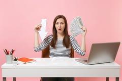 La flèche frustrante de chute de valeur de maintien de femme, sorts de paquet de dollars encaissent le travail d'argent au bureau image stock