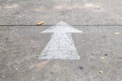 La flèche peinte par blanc de plan rapproché se connectent le fond de plancher de rue de ciment Photos libres de droits
