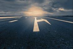 La flèche signe comme marquage routier sur une route de désert Photo libre de droits