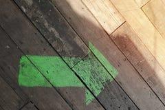 La flèche verte sur le plancher en bois, vident avec l'espace de copie pour le texte photographie stock
