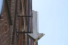 La flecha abajo firma en un housewall Imagenes de archivo