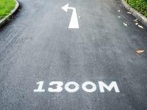 La flecha de la curva de la izquierda señala una trayectoria marcada del funcionamiento 1.300 metros Fotografía de archivo libre de regalías