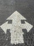La flecha de tres vías blanca de la dirección canta en los ladrillos de piedra Foto de archivo libre de regalías