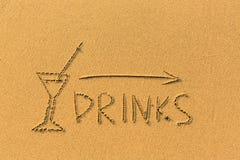 La flecha del indicador, el vidrio y las bebidas de las palabras dibujadas en la arena varan Feliz imagen de archivo libre de regalías