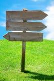 La flecha direccional de madera del cruce firma el prado Foto de archivo
