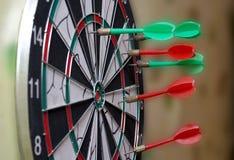 La flecha roja y verde del dardo golpeó al tablero Imagen de archivo