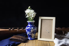 La fleur blanche dans le portefeuille bleu de cuir de vase et la photo encadrent l immobile Images stock