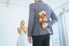 La fleur de dissimulation de marié derrière la jeune mariée étonnée de dos sur le jour du mariage, l'émotion positive de femme et photographie stock libre de droits