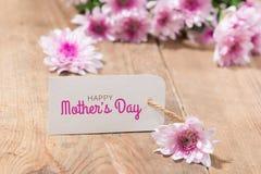 la fleur de jour donne à des mères le fils de momie à Étiquetez le papier avec des fleurs de couleur sur le fond en bois Images libres de droits