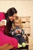 la fleur de jour donne à des mères le fils de momie à Enfant et mère buvant du chocolat chaud Photo stock
