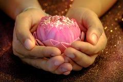 La fleur de lotus rose pliant le style thaïlandais dans a équipe la main pour le religio photo libre de droits