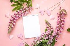 La fleur de loup et ouvrent le bloc-notes vide sur le fond rose l'espace Photo stock