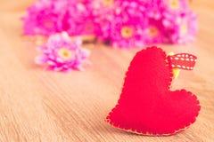 La fleur rose et les coeurs rouges forment sur le fond en bois de table, Photo stock