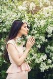 La fleur sentante de jeune femme parfaite en ressort de fleur fleurit Photos stock