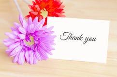 La flor artificial en colores pastel y el papel de nota blanco con le agradecen tex Fotografía de archivo libre de regalías