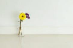 La flor colorida artificial del primer en la botella de cristal transparente en piso de mármol borroso y la pared del cemento bla Fotos de archivo