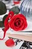 La flor de la rosa del rojo con una pila de postal, las fotos retras y el vintage reservan Fotos de archivo