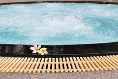 La flor del Plumeria y la piscina azul ondularon el detalle del agua Imagen de archivo libre de regalías