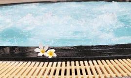 La flor del Plumeria y la piscina azul ondularon el detalle del agua Imágenes de archivo libres de regalías
