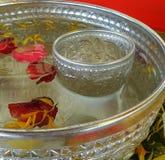 La flor fragante pedals nd en agua potable fría en el cuenco de plata para el festival de Songkarn Foto de archivo