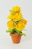 La flor plástica en los potes en el fondo blanco Fotos de archivo libres de regalías