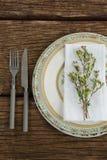 La flora y la servilleta arreglaron en la placa con los cubiertos Imagen de archivo libre de regalías