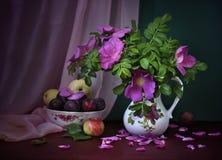 La floraison a monté dans une cruche et un fruit. Images libres de droits