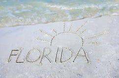 La Floride et le soleil dessinés en sable sur la plage avec une vague Photographie stock