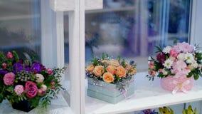 La floristería, en la demostración-ventana, allí es muchos ramos de las flores, composiciones elegantes florales en cajas colorid almacen de metraje de vídeo