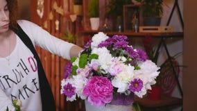 La floristería, florista Arranging Modern Bouquet, los floristas hermosos jovenes trabaja en la tienda de flores que hace el ramo almacen de metraje de vídeo
