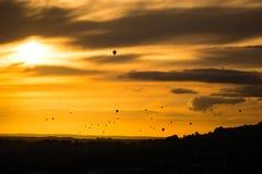 La flota de aire caliente hincha delante de puesta del sol sobre baño Foto de archivo