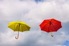 La flotación amarilla y roja del paraguas o de los parasoles suspendió en el aire imagen de archivo libre de regalías