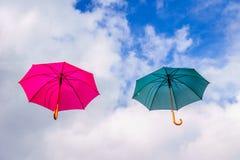 La flotación rosada y verde del paraguas o de los parasoles suspendió en el aire foto de archivo