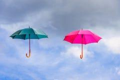 La flotación rosada y verde del paraguas o de los parasoles suspendió en el aire imágenes de archivo libres de regalías