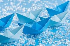 La flotte de papier bleu d'origami se transporte sur l'eau bleue comme le fond Photos libres de droits