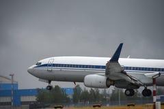 La fodera di passeggero decolla nel cielo dalla pista dell'aeroporto in tempo nuvoloso con pioggia Fotografia Stock