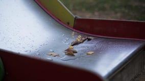 La foglia degli alberi sui bambini bagnati fa scorrere in parco nave nessuno Foglia playground archivi video