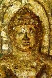 La foglia di oro Buddha coperto affronta. Immagine Stock