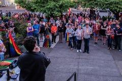 La folla con i simboli e le candele dell'arcobaleno ascolta l'altoparlante circa le fucilazioni di Orlando Fotografia Stock Libera da Diritti