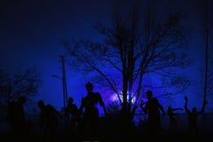 La folla degli zombie affamati si avvicina agli edifici residenziali Immagine Stock