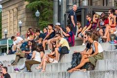 La folla dei turisti si siede sulle scale nazionali del palazzo a Barcellona Immagini Stock Libere da Diritti