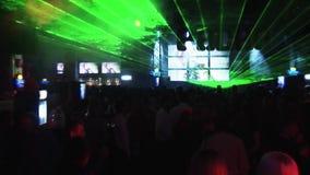 La folla della gente balla sul partito in night-club Fasci verdi variopinti dalla manifestazione del laser intrattenimento archivi video